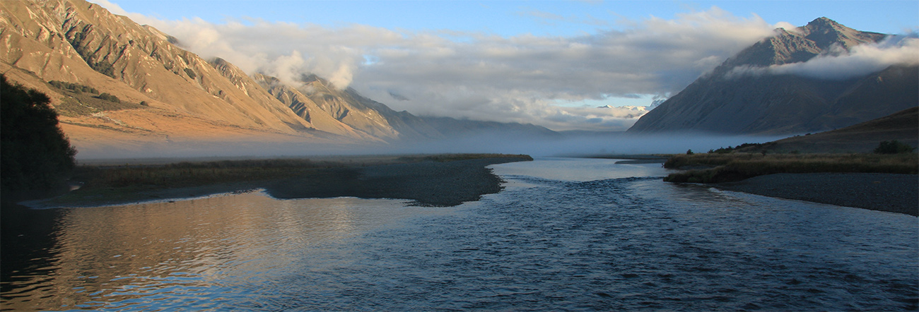 Ahuriri River, South Island, New Zealand, at daybreak with mist hanging over the water and left mountains illumined by rising sun