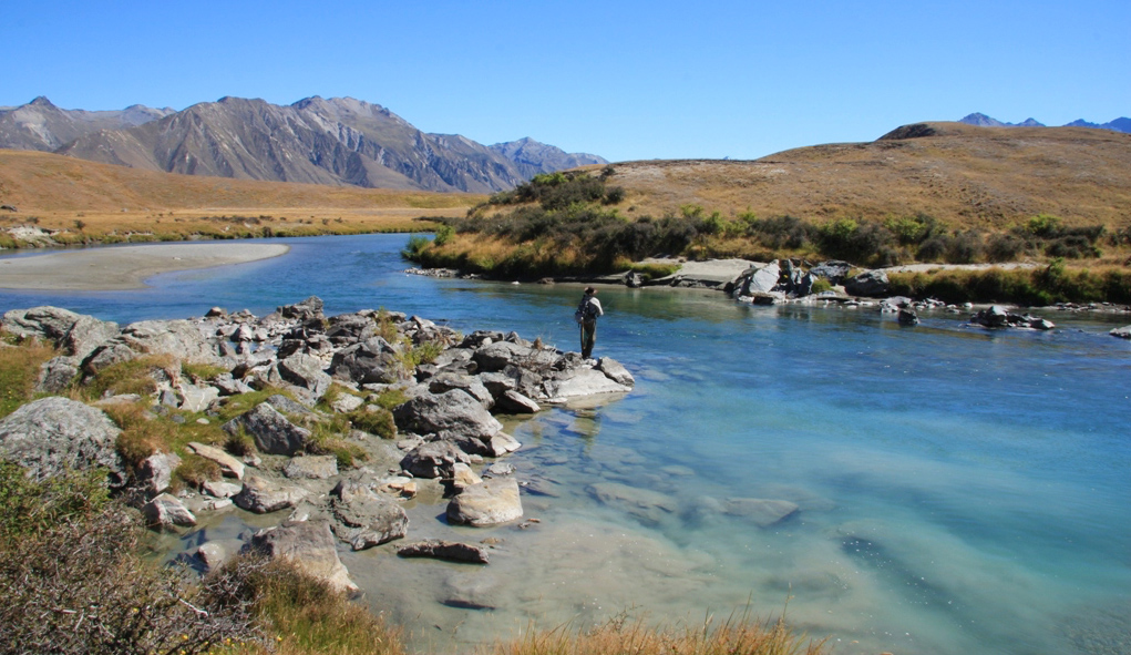 fly fisherman stands looking for trout in wide view of Ahuriri River with valley in background