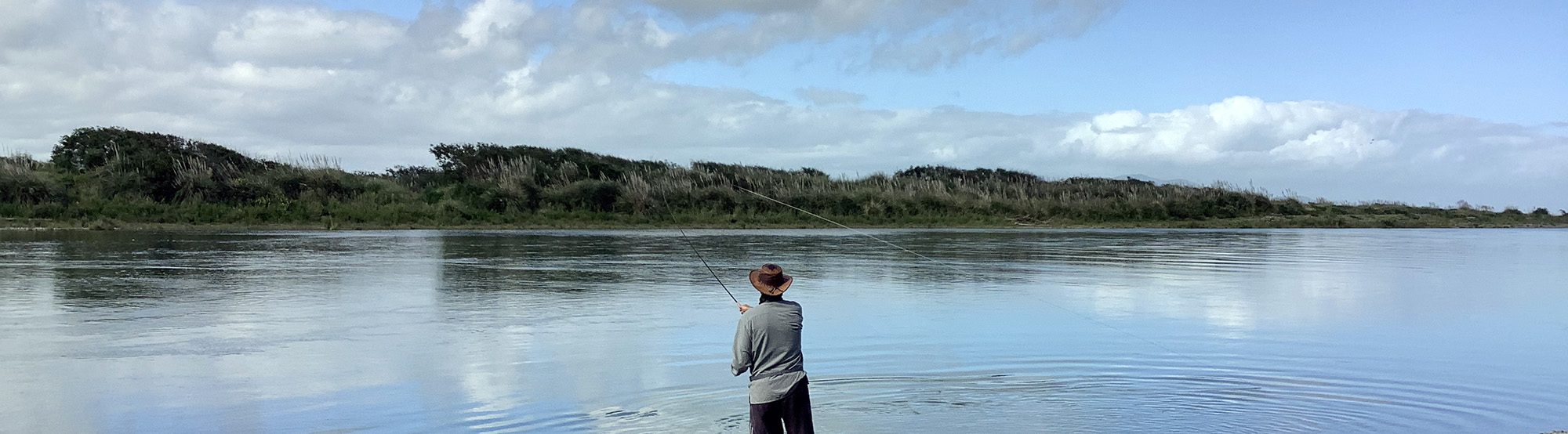 man-wearing-hat-double-spey-casting-on-river