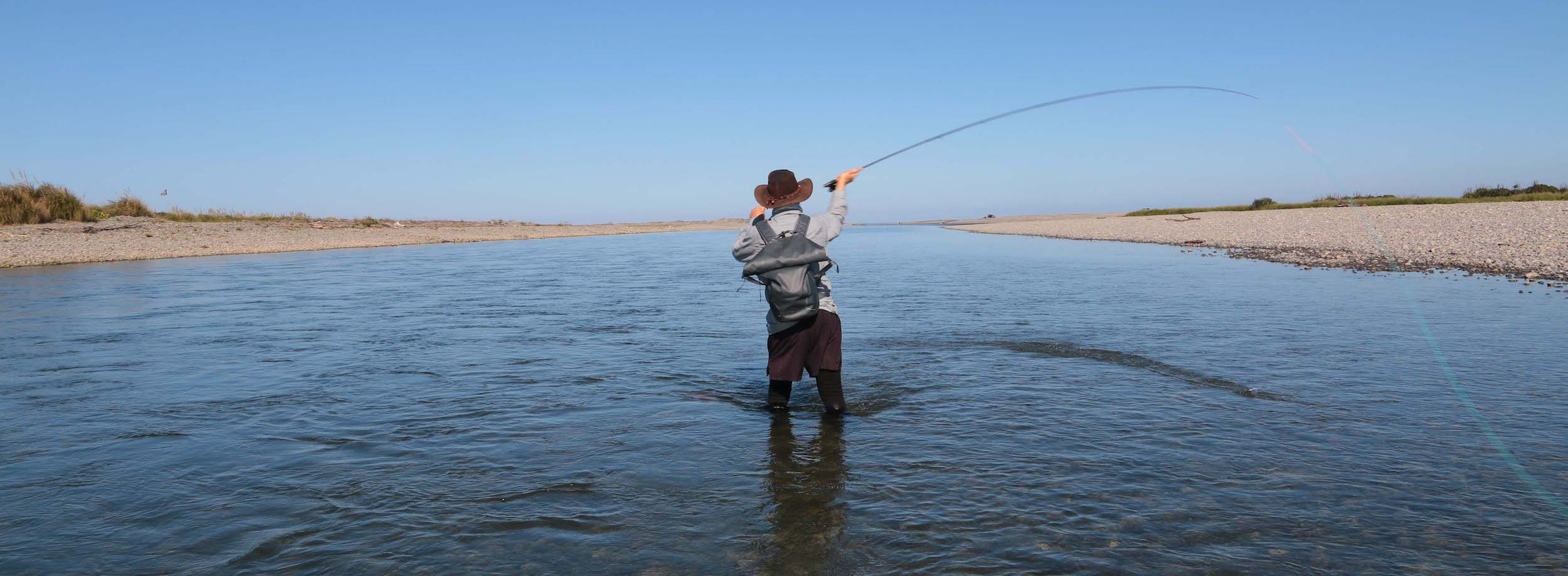 Fly fisherman, from behind, standing Spey casting in wide river mouth, using single-hand Spey rod, skagit head, line and sink tip
