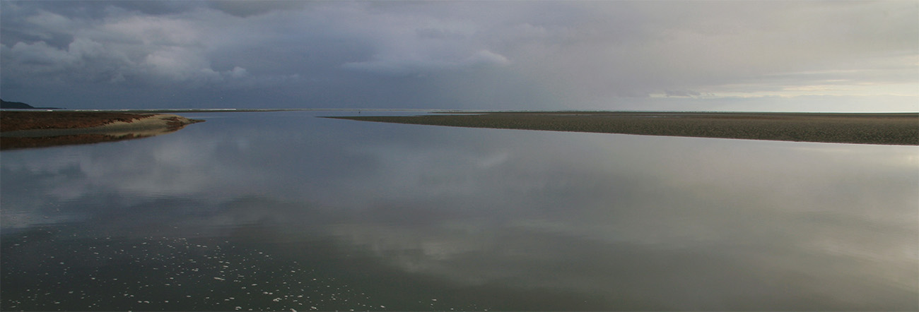 Very calm estuary before first light, muted tones of sky reflected on water's surface